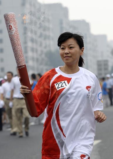 图文-奥运圣火北京首日传递 火炬手周继红