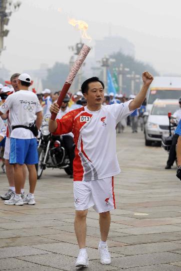 图文-奥运圣火北京首日传递 火炬手于凯奋力挥舞拳头