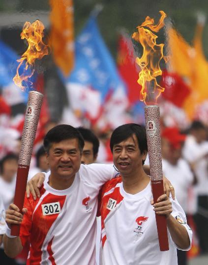 图文-奥运圣火在四川成都传递 任卫新与骆家辉交接