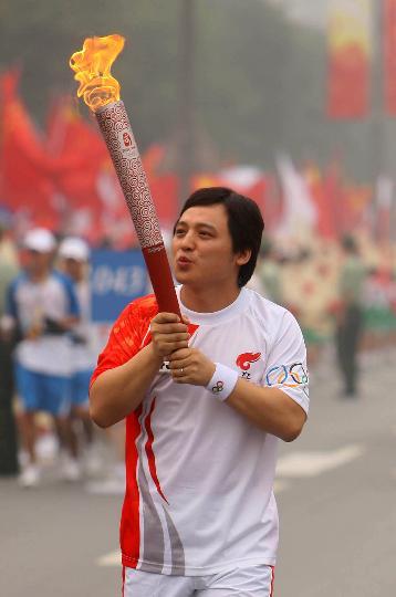 图文-奥运圣火最后一日传递 王大为手持火炬传递