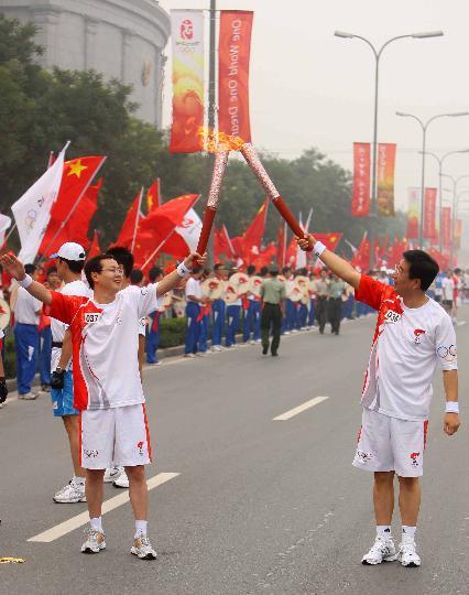 图文-奥运圣火最后一日传递 王辰与张成刚交接火炬