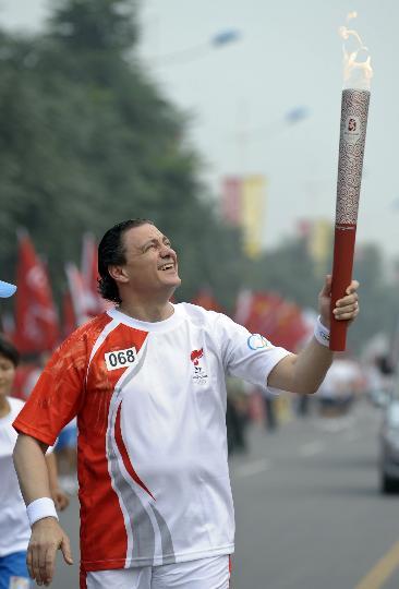 图文-奥运圣火最后一日传递 理查德手持火炬传递
