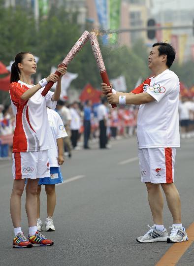 图文-奥运圣火最后一日传递 张春江与杜鹃交接火炬