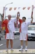 图文-奥运圣火最后一日传递 张伯旭与内维尔交接火炬