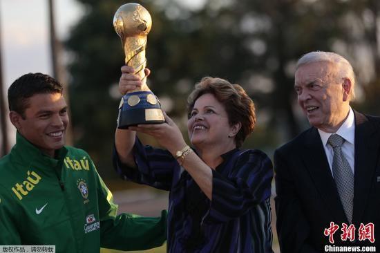 资料图:2013年9月2日,巴西巴西利亚,巴西总统罗塞夫(Dilma Rousseff)接见巴西国家足球队,并高举联合会杯的冠军奖杯。