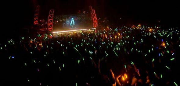 """""""初音未来""""与一支现场伴奏乐队一同登台表演,数千名歌迷挥舞着荧光棒,聆听她的美妙歌声。"""
