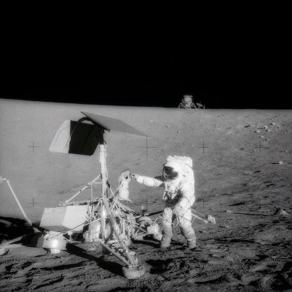 宇航员们拆卸下了勘测者-3号的相机和几件其他部件运回地球进行分析。这幅照片中,阿波罗-12号宇航员彼得•康拉德在着手拆卸前仔细查看勘测者-3号上的相机设备