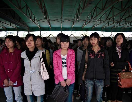 在富士康求职中心的门内,充满期待的求职者被按性别分开。一些人仍带着行李,他们经过了几天的旅途才来到这里。