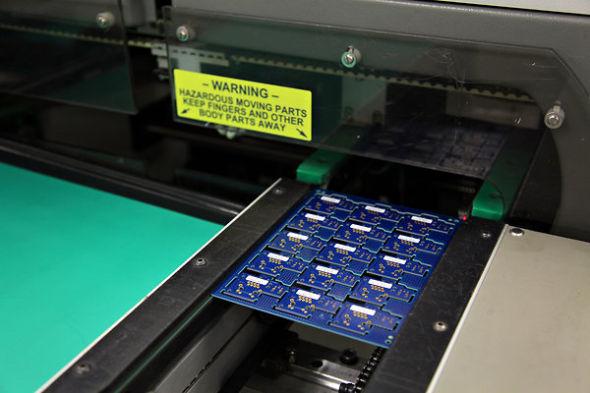 制造工厂,机器将芯片焊接到电路板上