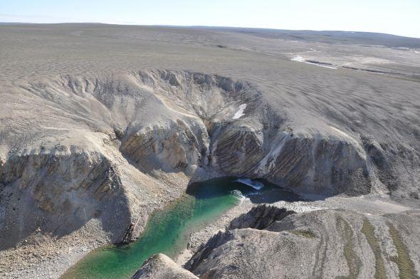 这是从直升机上拍摄的该地区河谷景色,可以看到直立翻转的沉积岩层。这种扭曲反映了撞击发生时中央地形反弹隆起的结果