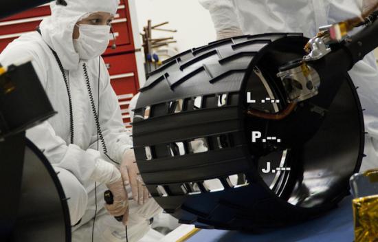 """""""好奇""""号车轮一个最令人吃惊的设计是每个车轮上有3排小孔,形状为字母J-P-L,代表喷气推进实验室"""