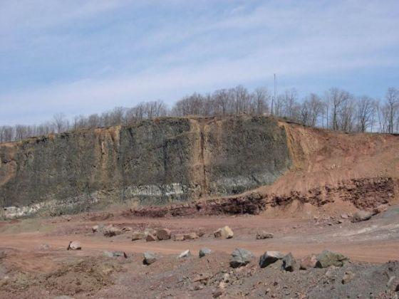 美国新泽西州克利夫顿的一个地区(曾经是采石场),左侧的黑色岩石由三叠纪末期的大规模玄武岩流形成,右侧的红色沉积层中存在物种大灭绝线索