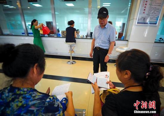 资料图:民众携带相关证件等待办理护照申请业务。刘新 摄