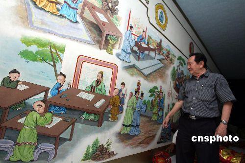 """资料图: 印尼解放禁锢了几十年的华文,使华文教育在印尼迎来了春天的机遇。拥有三十多年历史、隶属印尼丹格朗文德庙的孔教学校,不但学�A�Z,还教授悠久中华故文化,学校也在众多老华人的捐助下立起三层大楼,从幼稚园、小学、初中和高中,学生人数目前已达一千七百多人。图为今冬孔教学校美术老师介绍墙上他创作的弟子学文化的图画。   印尼雅加达班芝兰唐人街:每个角落皆有""""古董""""级纪录"""