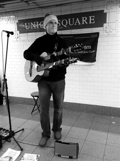 艺人斯科特在地铁中弹吉他。