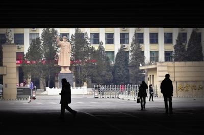 透过和平东桥与和平西桥相连的三环路高架桥桥洞看北京化工大学正门和院内挥手的毛主席雕像。