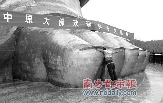 """昨日,河南平顶山鲁山县的中原大佛景区,景区工作人员在模拟""""抱佛脚""""。"""
