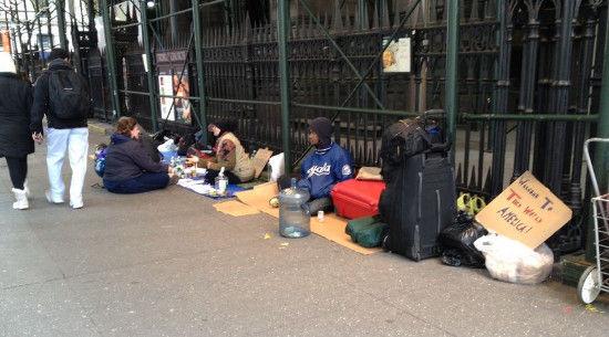华尔街街口正对面的教堂门前,无家可归者席地乞讨。(图片来源:新浪财经纽约站 罗绮梅 摄)