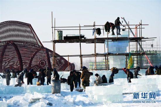 """在哈尔滨冰雪大世界园区,工人们在进行冰建筑施工(12月14日摄)。又是一年冰雪季,广袤的黑龙江大地上各种形式的冰雪活动先后拉开序幕。曾被不少当地人""""抱怨""""的寒冰冻雪正变成炙手可热的旅游资源。新华社记者王建威摄"""