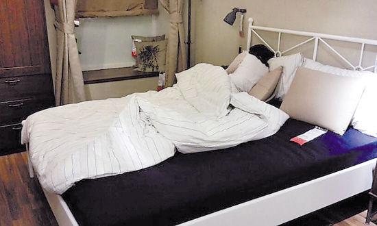 在广州宜家店内,一位顾客躺在样板床上休息