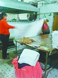 上图:工人徒手折叠熨烫好的床单