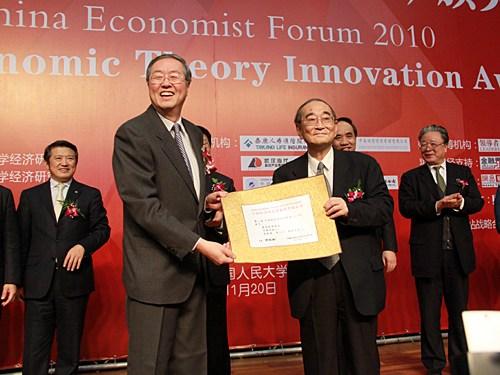 """""""中国经济学家年度论坛暨中国经济理论创新奖(2010)颁奖典礼""""于2010年11月20日在中国人民大学举行。上图为厉以宁为周小川颁发获奖证书。(图片来源:新浪财经 梁斌 摄)"""