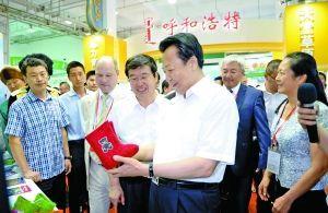 7月19日上午,自治区领导王君(中)、巴特尔(左四)参观第七届中国民族商品交易会呼和浩特展区。本报记者 袁永红 摄