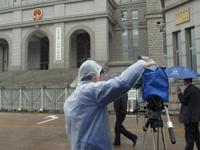 媒体披着雨披对着空旷的法院门口拍摄