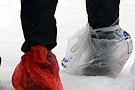 市民脚上系塑料袋雪中步行
