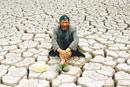 农民做在干涸诶对土地上