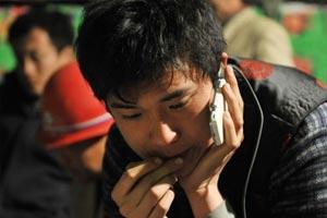 玉树强震第四天:李帅在玉树县结古镇通信站点给远在河南南阳的家人打电话报平安