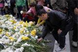 众人为死者献花