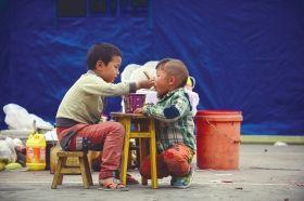 4月21日上午,龙门乡,龙门晨阳希望小学操场,两个小孩子正在共享一碗方便面。图/记者谢长贵