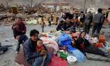 图文:人们在倒塌房屋前临时安置