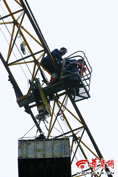 有人爬上塔吊后,将绳子一头拴在塔吊大臂上,另一头绑在身上,正悬在半