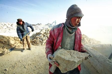 一名智障工人正在搬运石头图据《新疆都市报》