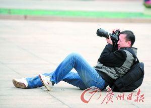 躺在地板上拍摄的记者。