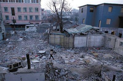 """一名小女孩从废墟上走过。位于东城区北总布胡同24号院的""""梁林故居""""已被拆除。新京报记者 孙纯霞 摄"""