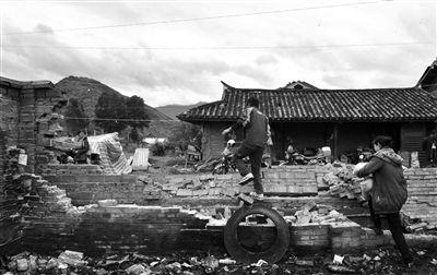 昨日,云南省永宁乡上开基村村民翻越坍塌的院墙。本版图片/新华社记者 陈海宁 摄
