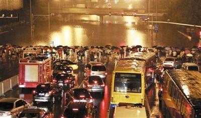 """7月21日,一场特大暴雨袭京,广渠门桥附近,道路积水严重,路人和车辆都被拦在一片""""汪洋""""前。新京报记者 谢家燕 摄"""