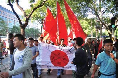 """昨天,群众在日本驻华大使馆附近打标语、喊口号,反对日本非法""""购买""""钓鱼岛。 本报实习记者杨昊宇摄"""