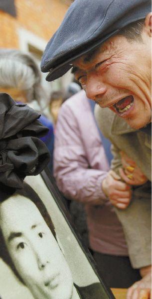 2003年12月18日,孙志刚葬礼,看着儿子的遗像,50多岁的孙禄松悲痛欲绝。 孙志刚的墓志铭末尾是: 以生命为代价推动中国法治进程。值得纪念的人――孙志刚。 (资料图片)