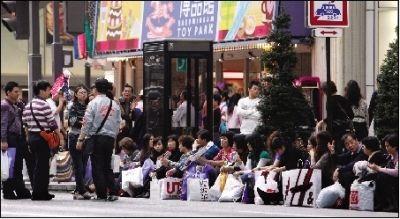2010年4月11日,日本东京,中国旅客在商店血拼后,坐在银座街头休息。图/IC
