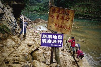 10月8日,几名少年在滑坡废墟前帮助大人清理淤泥。附近孩子上学都是走这样的路。