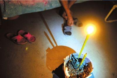 26日,芦山县龙门乡隆兴村村民张德文在帐篷中点燃香烛。他的妻子在地震中不幸遇难。 新华社发