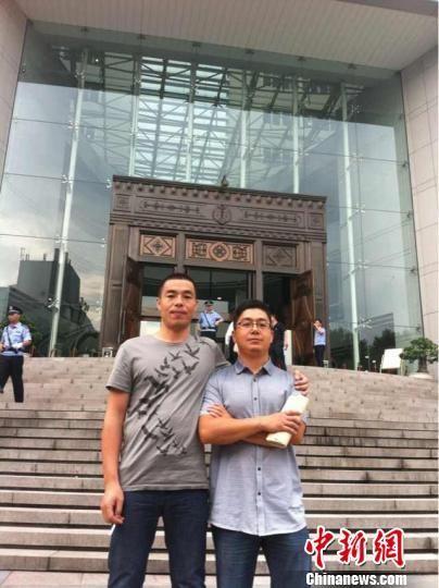 图为陈建阳(左一)和田伟东在浙江省高级人民法院门口合影。 赵小燕 摄