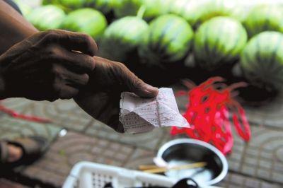 ▲瓜农向记者出示当地城管之前给他开的摆摊收据。 京华时报记者 潘之望摄