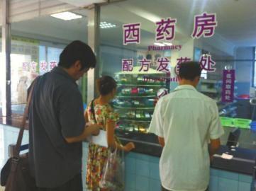 成都市卫生局中医处处长卢洪岩(左一)在等待取药。