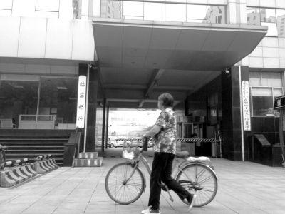 9月10日,一位市民扶着自行车从临商银行某支行门前走过。