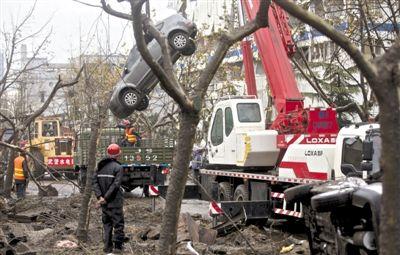 输油管道爆炸后,抢修人员将被炸毁的车辆运出现场。